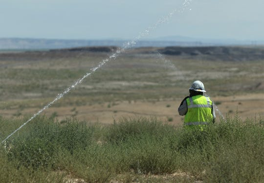 A Navajo Mine employee checks sprinklers in a recently seeded part of the mine.