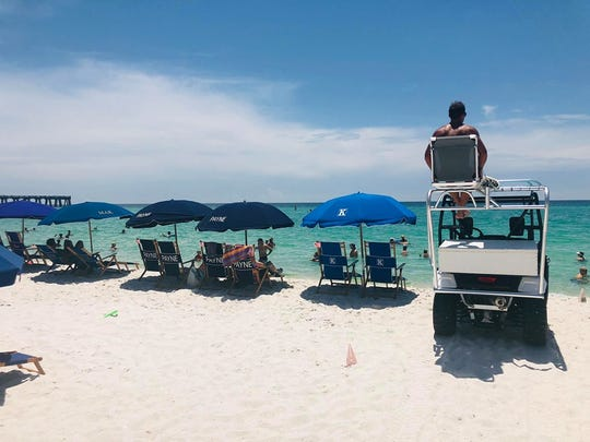 Navarre Beach Safety Supervisor Aaron Telatovich observes beachgoers from atop a custom ATV outfitted with a built-in tower that Beach Safety Chief Austin Turnbull designed and built himself.