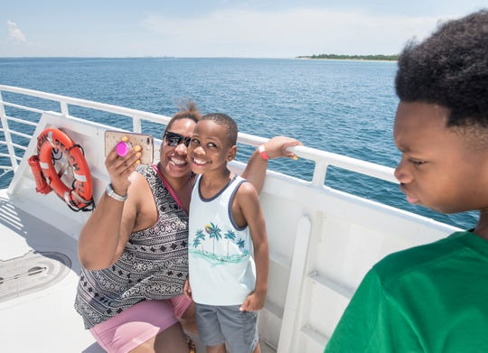 Carson Brown, 6, sneaks a peek at Jailen Jones, 12, as he and his mother Rescindia Brown, of Shreveport, Louisiana, snap a selfie onboard the Pelican Perch ferry on Thursday.