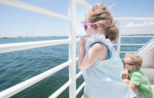 Ellie Sadlow, 3, and her brother Andrew Sadlow, 5, watch as the Pelican Perch ferry approaches the Quietwater/Pensacola Beach dock during a Pensacola Bay Cruise on Thursday, August 1, 2019.