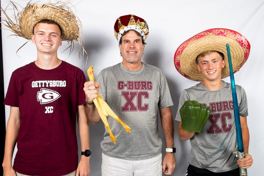 Gettysburg cross country runners Andrew Hirneisen (left) and Drew Cole (right) strike a pose with coach Brian Mount in the GameTimePA photo booth during YAIAA fall sports media day in Hanover on Friday, August 2, 2019.