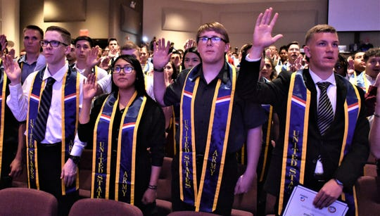 Future soldiers being recognized for enlisting in the U.S. Army, raise their right hands while reciting the oath of enlistment, at the third annual 2019 Induction Ceremony, April 26, Calvary Community Church, Glendale, Ariz.