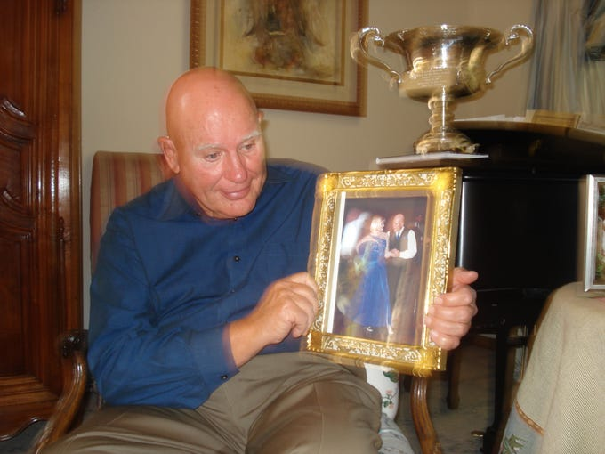 Jack Clifford shows a photo of him dancing with his wife of 49 years, Margeurite Clifford. She died in 2007. The couple loved to compete in ballroom dancing competitions; a photo of a dancing trophy sits behind Jack on the piano.