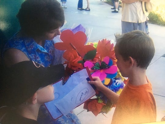 First-grade students filled the arms of teacher Susan Ashcraft with paper flowers and gift cards on Teacher Appreciation Day.