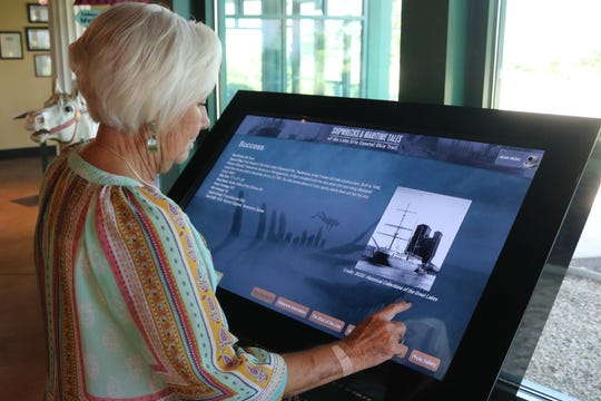 "Jeanette Cox checks out the story of the ""Success,"" a former 1800s prison ship retired after being burned by vandals in Port Clinton in 1939, which is among the dozens included in the shipwrecks exhibit at the Lake Erie Shores and Islands Visitors Center."