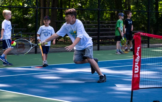 Zachary Roosen, 10, reaches for the ball with his racket during a game on Kids Day at the Francis J. Robinson Memorial International Tennis Tournament Friday, Aug. 2, 2019, at Sanborn Park.