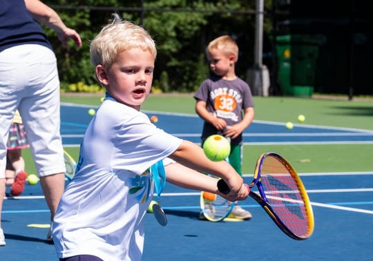 Andrew Wallbank, 4, swings for the ball on Kids Day at the Francis J. Robinson Memorial International Tennis Tournament Friday, Aug. 2, 2019, at Sanborn Park.