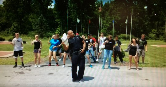 "Officer Tim Davis and participants in Richmond Police Department's Youth Police Academy dance ""The Git Up"" at Veterans Memorial Park."