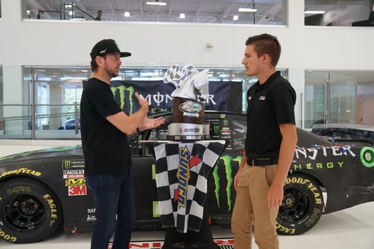 Greece native Elijah Burke, right, with NASCAR driver Kurt Busch at Chip Ganassi Racing facilities in Concord, North Carolina. Burke handles sales, social media and eSports for Ganassi, which has race teams in NASCAR, Indy Car and other pro series.