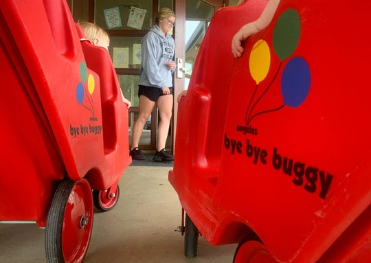 Kaylee Landsem, an assistant at the Salem Child Development Center, Liberty Gardens site, holds the door open so teachers can push their six-seat buggies back into the building August 2, 2019. The two 'bye bye buggies' were purchased from the YMCA as they cleaned out their 110,000-square-foot building downtown. The center, which is happy to have the new buggies, purchased them for $200 apiece. The Salem Family YMCA downtown will soon be demolished to make room for a new facility that is expected to open in spring 2021.