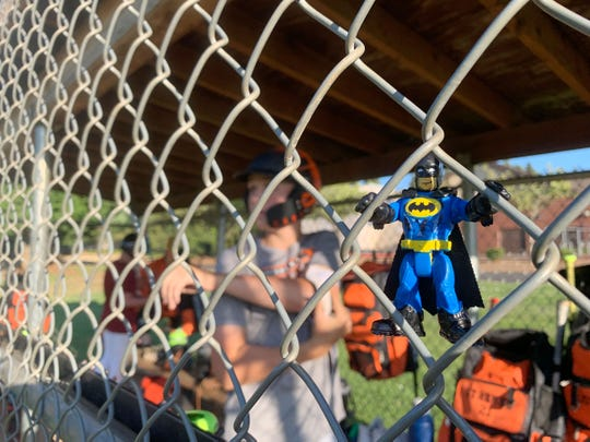 A Batman figurine hangs on the dugout as the Sprague Little League baseball team practices at Crossler Middle School, July 31, 2019. The team will represent Oregon at the NW Regionals this weekend.