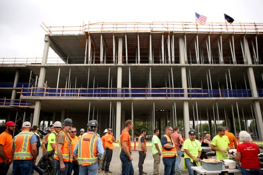 Construction works, police officers and guests line up for lunch following a topping out ceremony at the new Salem Police headquarters on Aug. 2, 2019. The structure, including concrete and steel, is now complete. Construction will move on to interior and exterior projects.