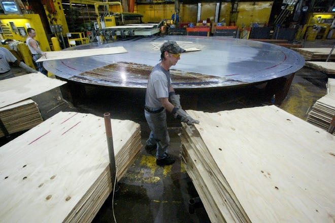 Workers at the Roseburg Forest Products Plywood Plant in Dillard, Oregon, are seen stacking plywood along a production line.