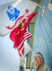 John Vierra, 91, of Keizer poses under flags that represent the branches of the military he served in. Vierra served in the Merchant Marine, Coast Guard, Marine Corps and Army over thee wars, World War II, Korea and Vietnam.