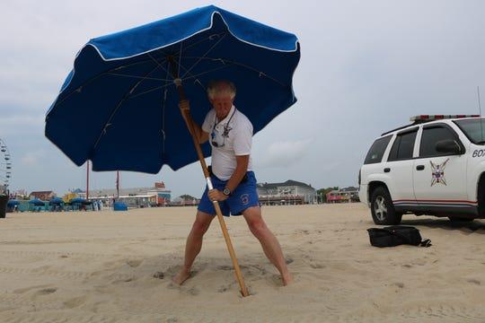 Ocean City Beach Patrol Capt. Butch Arbin demonstrates the proper way to set up a beach umbrella in Ocean City on Aug. 2.