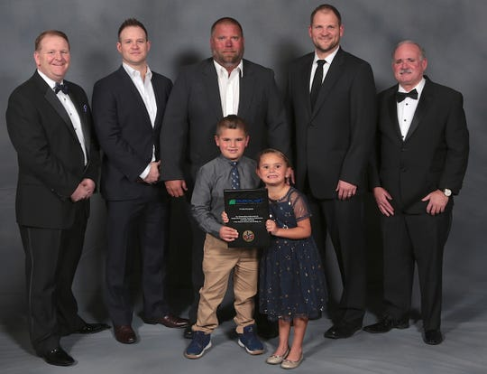 Precision Roofing Services Project Supervisor Tim Steiner (center) and his children are shown with representatives from Duro-Last, Inc. displaying the Admiral Club award the company received at Duro-Last's national sales meeting in Florida.