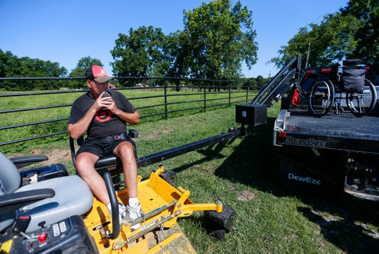 Doug Boswell, 54, who is paralyzed from the waist down, sits on a chair lift attached to his truck that allows him to get into and out of farm equipment on Tuesday, July 30, 2019.