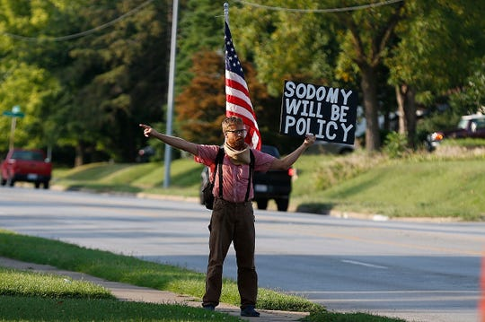 A protester outside at the story-sharing meeting hosted by Springfield NAACP and community partners at National Avenue Christian Church in Springfield, Mo. on Aug. 1, 2019