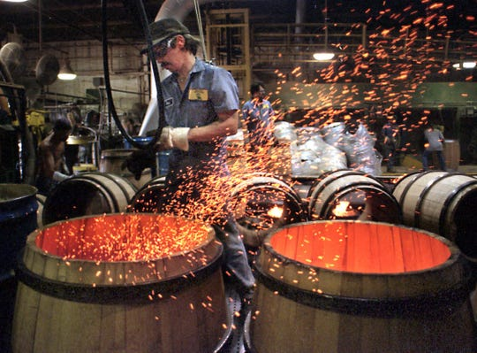 In this 1999 file photo, an Independent Stave Company worker watches fires burning inside new wine barrels at a plant in Lebanon. OSHA fined a subsidiary company $413,000 on Aug. 2, 2019 for violations including repeated amputations.