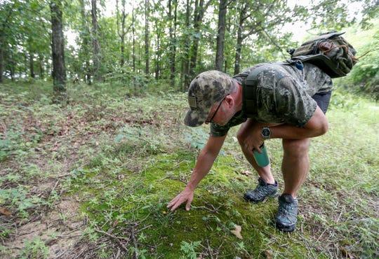 Chris Miller checks out a small chanterelle mushroom in the woods near Stockton Lake on Thursday, Aug. 1, 2019.