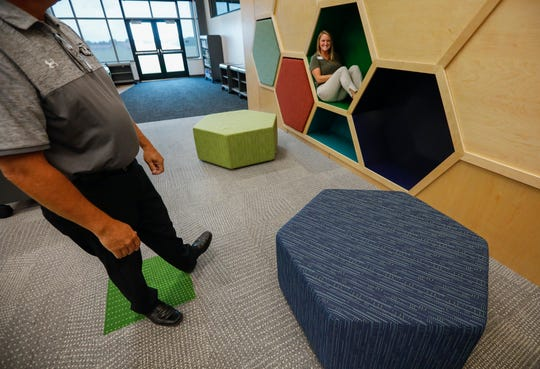 Whitney Burrell, who oversees communications for the district, sits inside one of the cubby holes inside the library at the new Willard Intermediate School-South.