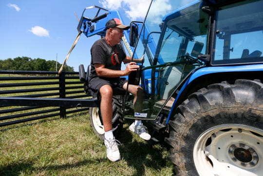 Using a chair lift attached to his truck, Doug Boswell, 54, positions himself to climb into his tractor on Tuesday, July 30, 2019.