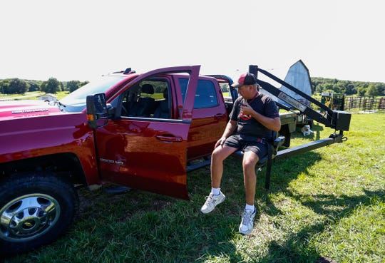 Using a chair lift attached to his truck, Doug Boswell, 54, who is paralyzed from the waist down, positions himself to get into the truck on Tuesday, July 30, 2019.