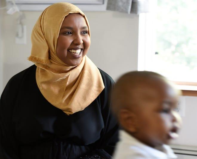 Fadumo Hassan smiles as her son, Maher, runs around their apartment Thursday, Aug. 1, 2019.
