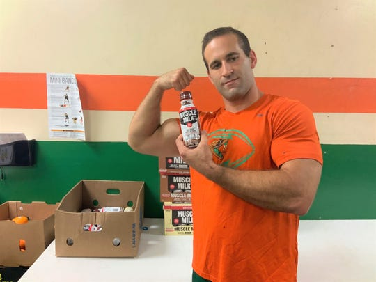 FAMU strength and conditioning coach Parker Brooks shows his pleasure upon receiving boxes of fruit, Gatorade and Muscle Milk from the 220 Quarterback Club.