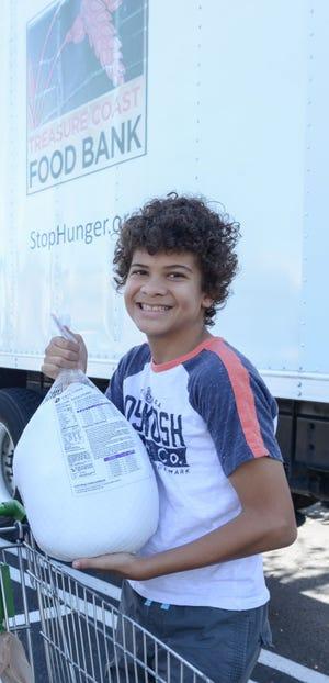 Treasure Coast Food Bank volunteer Esteban Gomes Lopez accepts a turkey donation.