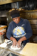 Boys & Girls Club member Laylah E. works the dough during a visit to Big Apple Pizza in Fort Pierce.