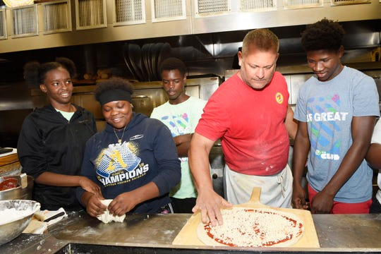 Big Apple Pizza owner Scott Van Duzer, center, shows how to make a pizza to Boys & Girls Club members Ta'miyah C., Laylah E., Alex A. and Sharmarko E.