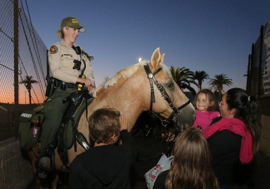 Judy Alvarez, right, of Santa Paula, holds her daughter Jayda, 4, as she pets Ventura County Sheriff's Deputy Amanda Foster's horse Nino with two other fairgoers as she patrols the Ventura County Fair on Thursday night. Foster is part of the Ventura County Sheriff's Mounted Enforcement Unit. The deputies' job is to just patrol the perimeter surrounding the fair but on occasions they are asked to assist the foot patrol inside the fair.