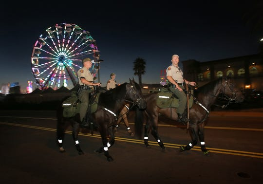 Ventura County Sheriff's deputies Robert Steele, from left, Amanda Foster and James Evans pass the Ferris wheel at the Ventura County Fair as they patrol Aug. 1, 2019.