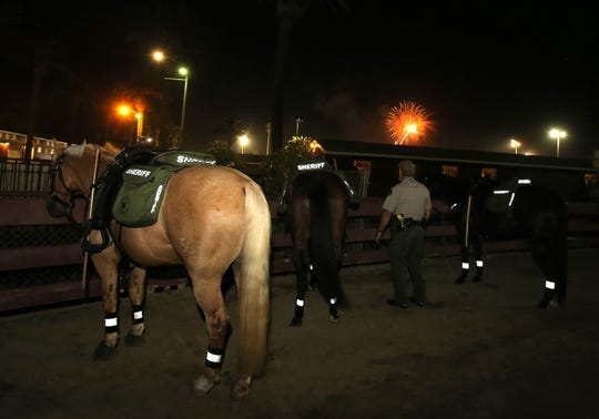 Ventura County Sheriff Deputy James Evans watches the fireworks from one of the arenas inside the Ventura County Fair on Thursday night. Evans is part of the Ventura County Sheriff's Mounted Enforcement Unit. The deputies normally just patrol the perimeter surrounding the fair but on occasions they have been asked to assist the foot patrol inside the fair.