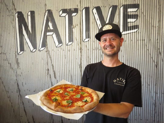 Native Pizza general manager Ryan Peck poses with The Original, a pizza made with pomodoro, fresh mozzarella, basil, grana and a drizzle of olive oil.