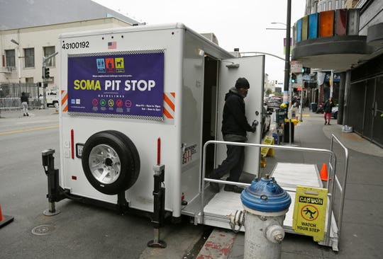 "An attendant exits a ""Pit Stop"" public toilet on Sixth Street on Aug. 1, 2019, in San Francisco. A 5-year-old portable toilet program in San Francisco that provides homeless people with a private place to go has expanded to 25 locations in the city and has spread to Los Angeles."