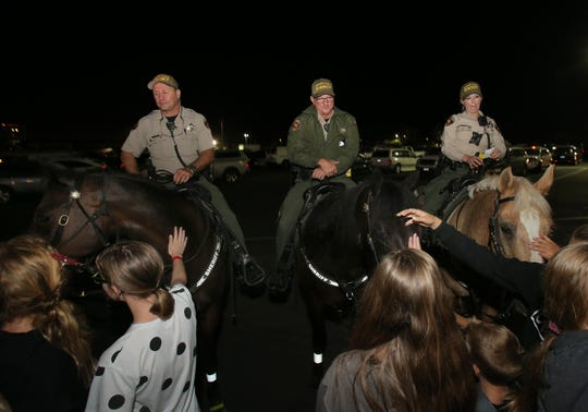 Ventura County Sheriff's deputies James Evans, from left, Robert Steele and Amanda Foster are greeted by fairgoers as they patrol the Ventura County Fair grounds on Thursday night. The Ventura County Sheriff's Mounted Enforcement Unit normally just patrols the perimeter surrounding the fair but on occasions they have been asked to assist the foot patrol inside the fair.