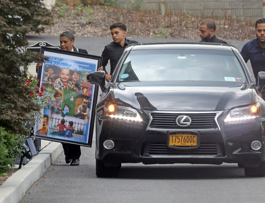 A woman carries a poster with photos of 1-year-old twins, Luna and Phoenix Rodriguez for their wake at Sinatra Memorial Home in Yonkers Aug. 2, 2019.