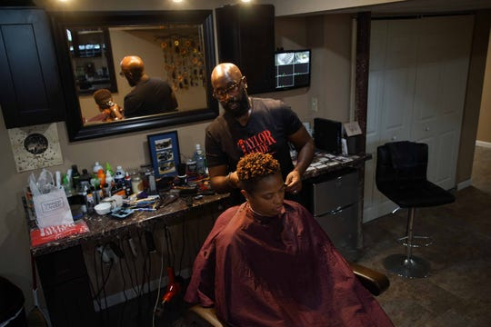 """Richard Taylor gives a cut to longtime client Dione Reeves, of Newark. After abruptly losing his job as a foster care social worker, Richard Taylor, opened his Delaware incorporated barbershop """"Taylor Made Cuts"""" in the basement of his home to help pay bills. Being self-employed has made him happier than he could ever imagine."""