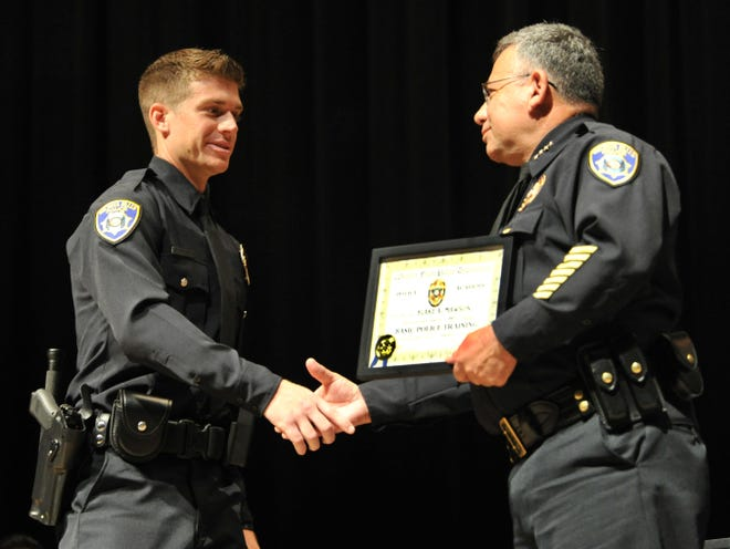 Wichita Falls Chief of Police Manuel Borrego, right, presented honor graduate and new police officer, Blake Mawson, his police academy certificate Friday morning during a ceremony held to celebrate the 72nd graduation from the academy.