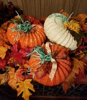 Once your spray-painted pumpkins dry, use a hot glue gun or regular glue and embellish however you like. Here, the artist used twigs from his yard, silk leaves and flowers and even some green Easter grass.