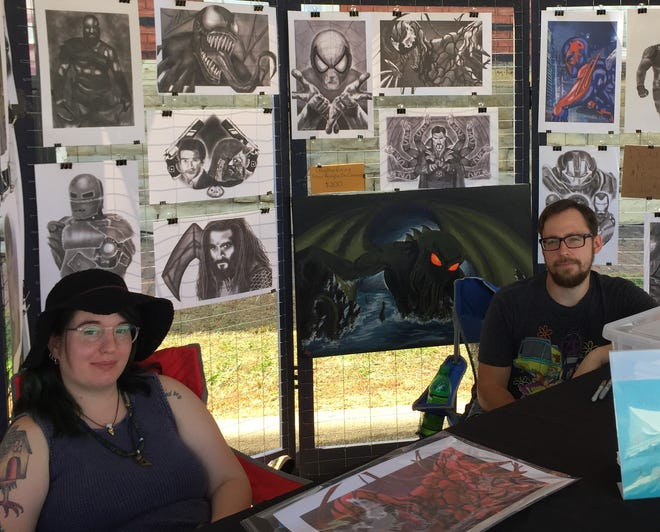 Morgan and Heath Langsdorf present Heath's digital art pieces at Zane's Landing Friday during the annual Y-Bridge Arts Festival.