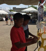 Darrius and Journ'te piece together art from disposable lids during the 11th annual Y-Bridge Arts Festival in downtown Zanesville Friday.