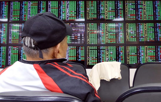 A man watches a monitor at a stock exchange in Taipei, Taiwan, 02 August 2019. Asian currencies and stocks fell after President Donald Trump announced new tariffs on Chinese goods.