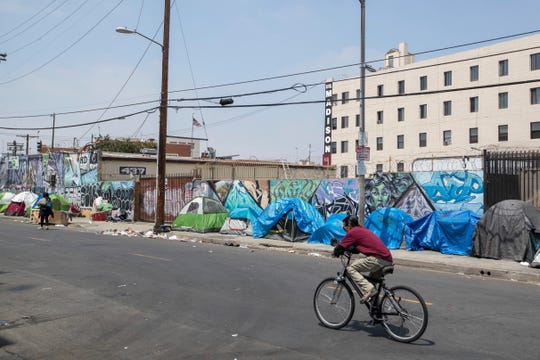 Homeless people and their tents line a Skid Row street on Friday, May 31, 2019 in Downtown Los Angeles.