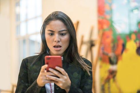 Business woman checks smartphone