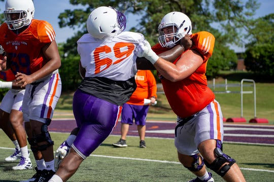 Senior offensive lineman Dustin Burns (right) blocks during a preseason camp workout.