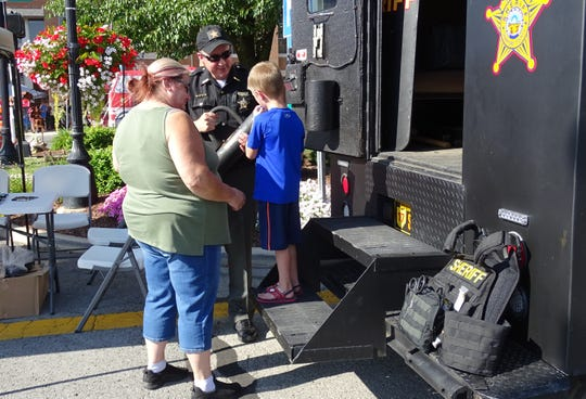 Crawford County Sheriff Scott Kent shows off gear from the Crawford County Special Response Team truck to Pamela Keuscher and Urijah Dyer, 5, during the August First Friday event downtown. The theme was hometown heroes.