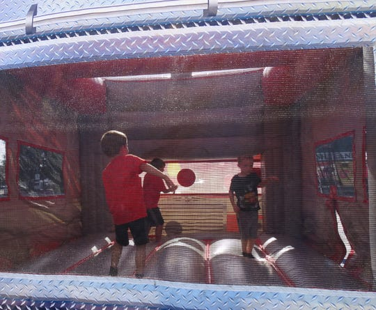 Kids play in the bounce house during the August First Friday event downtown.